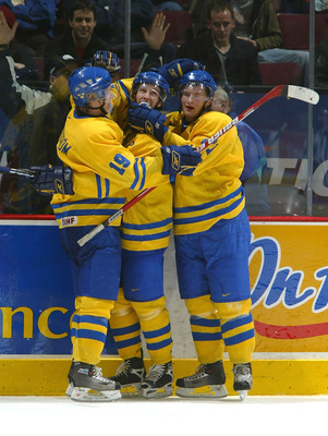 VANCOUVER - JANUARY 4:  Nicklas Bergfors #19, Mattias Ritola #21, both of Team Sweden, congratulate teammate Sebastian Karlsson #3 after he scored an empty net goal during their World Jr. Hockey Championship 5th place game on January 4, 2006 at General Mo