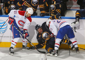 BUFFALO, NY - JANUARY 18: Scott Gomez #11 and Brian Gionta #21 of the Montreal Canadiens trap Patrick Kaleta #36 of the Buffalo Sabres against the boards at HSBC Arena on January 18, 2011 in Buffalo, New York.  (Photo by Rick Stewart/Getty Images)