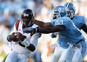 CHAPEL HILL, NC - NOVEMBER 13:  Tyrod Taylor #5 of the Virginia Tech Hokies is tackled by Bruce Carter #54 and teammate Jared McAdoo #97 of the North Carolina Tar Heels during their game at Kenan Stadium on November 13, 2010 in Chapel Hill, North Carolina