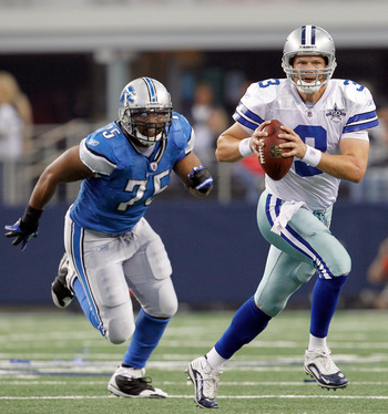 ARLINGTON, TX - NOVEMBER 21:  Quarterback Jon Kitna #3 of the Dallas Cowboys scrambles with the ball against defensive end Turk McBride #75 of the Detroit Lions at Cowboys Stadium on November 21, 2010 in Arlington, Texas.  The Cowboys beat the Lions 35-19