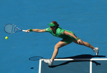 MELBOURNE, AUSTRALIA - JANUARY 20:  Kim Clijsters of Belgium stretches to play a forehand in her second round match against Carla Suarez Navarro of Spain during day four of the 2011 Australian Open at Melbourne Park on January 20, 2011 in Melbourne, Austr