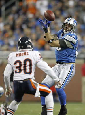 DETROIT - DECEMBER 05: Tony Scheffler #85 of the Detroit Lions makes a catch as D. J. Moore #30 of the Chicago Bears defends during the fourth quarter of the game at Ford Field on December 5, 2010 in Detroit, Michigan. The Bears defeated the Lions 24-20.
