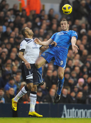 LONDON, ENGLAND - DECEMBER 28: Andy Carroll of Newcastle United wins a header against Younes Kaboul of Tottenham Hotspur during the Barclays Premier League match between Tottenham Hotspur and Newcastle United at White Hart Lane on December 28, 2010 in Lon
