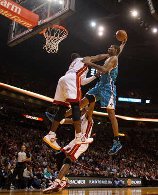 MIAMI, FL - DECEMBER 13:  Trevor Ariza #1 of the New Orleans Hornets dunks over Dwyane Wade #3 of the Miami Heat during a foul shot during a game at American Airlines Arena on December 13, 2010 in Miami, Florida. NOTE TO USER: User expressly acknowledges