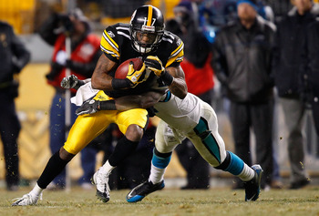 PITTSBURGH - DECEMBER 23:  Mike Wallace #17 of the Pittsburgh Steelers attempts to break a tackle after catching a pass against the Carolina Panthers during the game on December 23, 2010 at Heinz Field in Pittsburgh, Pennsylvania.  (Photo by Jared Wickerh