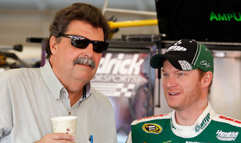 FONTANA, CA - OCTOBER 09:  Dale Earnhardt Jr., driver of the #88 National Guard/AMP Energy Chevrolet, stands in the garage with NASCAR President Mike Helton during practice for the NASCAR Sprint Cup Series Pepsi Max 400 on October 9, 2010 in Fontana, Cali