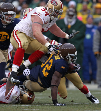 GREEN BAY, WI - DECEMBER 05: Brandon Jackson #32 of the Green Bay Packers is tackled by Shawntae Spencer #36 and Ahmad Brooks #55 of the San Francisco 49ers as Justin Smith #94 closes in at Lambeau Field on December 5, 2010 in Green Bay, Wisconsin. The Pa