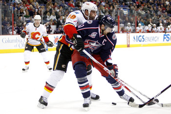 COLUMBUS, OH - DECEMBER 21:  Robyn Regehr #28 of the Calgary Flames and Rick Nash #61 of the Columbus Blue Jackets battle for control of a loose puck during the second period on December 21, 2010 at Nationwide Arena in Columbus, Ohio.  (Photo by John Grie