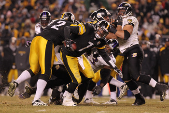 PITTSBURGH, PA - JANUARY 15:  Quarterback Ben Roethlisberger #7 of the Pittsburgh Steelers breaks a tackle by defensive end Cory Redding #93 of the Baltimore Ravens in the AFC Divisional Playoff Game at Heinz Field on January 15, 2011 in Pittsburgh, Penns