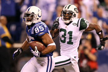 INDIANAPOLIS, IN - JANUARY 08:  Pierre Garcon #85 of the Indianapolis Colts scores on a 57-yard touchdown reception in the seocnd quarter against Antonio Cromartie #31 of the New York Jets during their 2011 AFC wild card playoff game at Lucas Oil Stadium