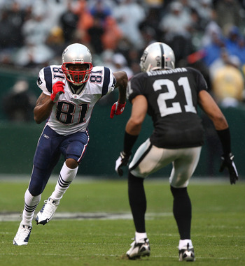 OAKLAND, CA - DECEMBER 14:  Randy Moss #81 of the New England Patriots runs against Nnamdi Asomugha #21 of the Oakland Raiders during an NFL game on December 14, 2008 at the Oakland-Alameda County Coliseum in Oakland, California.  (Photo by Jed Jacobsohn/
