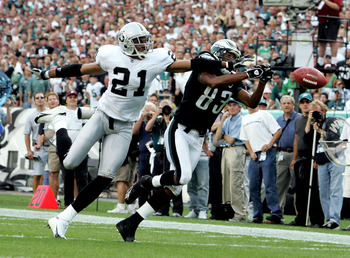 PHILADELPHIA - SEPTEMBER 25:  Wide receiver Greg Lewis #83 of the Philadelphia Eagles reaches for a pass against cornerback Nnamdi Asomugha #21 of the Oakland Raiders during their game on September 25, 2005 at Lincoln Financial Field in Philadelphia, Penn