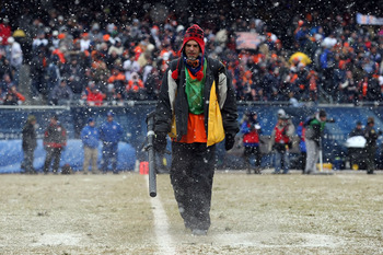 CHICAGO, IL - JANUARY 16:  A member of the field crew blows the snow off the yardage lines in the second quarter of the 2011 NFC divisional playoff game between the Seattle Seahawks and the Chicago Bears at Soldier Field on January 16, 2011 in Chicago, Il