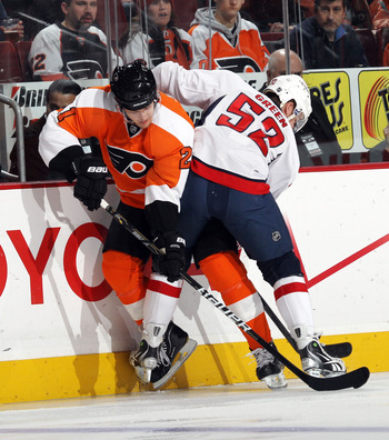PHILADELPHIA, PA - JANUARY 18: Mike Green #52 of the Washington Capitals hits James van Riemsdyk #21 of the Philadelphia Flyers into the boards at the Wells Fargo Center on January 18, 2011 in Philadelphia, Pennsylvania. (Photo by Bruce Bennett/Getty Imag