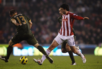 STOKE ON TRENT, ENGLAND - DECEMBER 28: Marc Wilson of Stoke City attempts to pass the ball past Danny Murphy of Fulham during the Barclays Premier League match between Stoke City and Fulham at Britannia Stadium on December 28, 2010 in Stoke on Trent, Engl