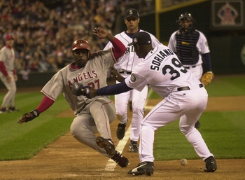 SEATTLE - APRIL 7:  Vladimir Guerrero #27 of the Anaheim Angels scores when Rafael Soriano #39 of the Seattle Mariners drops the ball on April 7 2004 at Safeco Field in Seattle, Washington. Soriano was charged with an error on the play.  (Photo by Otto Gr