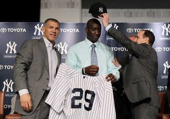 NEW YORK, NY - JANUARY 19:  Rafael Sorianoof the New York Yankees is presented his jersey and cap from manager Joe Girardi (L) and general manager Brian Cashman during his introduction press conference on January 19, 2011 at Yankee Stadium in the Bronx bo