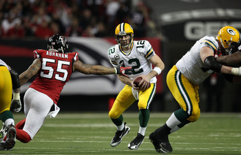 ATLANTA, GA - JANUARY 15:  Aaron Rodgers #12 of the Green Bay Packers elludes the pass rush of John Abraham #55 of the Atlanta Falcons during their 2011 NFC divisional playoff game at Georgia Dome on January 15, 2011 in Atlanta, Georgia.  (Photo by Street