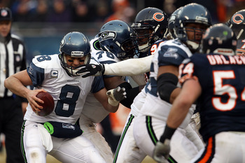 CHICAGO, IL - JANUARY 16:  Quarterback Matt Hasselbeck #8 of the Seattle Seahawks attempts to avoid a sack by Julius Peppers #90 of the Chicago Bears in the second half in the 2011 NFC divisional playoff game at Soldier Field on January 16, 2011 in Chicag