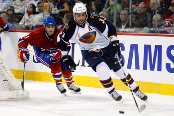 MONTREAL, CANADA - JANUARY 2:  Dustin Byfuglien #33 of the Atlanta Thrashers skates with the puck while being chased by Scott Gomez #11 of the Montreal Canadiens during the NHL game at the Bell Centre on January 2, 2011 in Montreal, Quebec, Canada.  The T