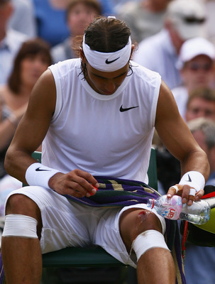 LONDON - JULY 04:  Rafael Nadal of Spain washes his cut knee with water during the men's singles Semi Final match against Rainer Schuettler of Germany on day eleven of the Wimbledon Lawn Tennis Championships at the All England Lawn Tennis and Croquet Club