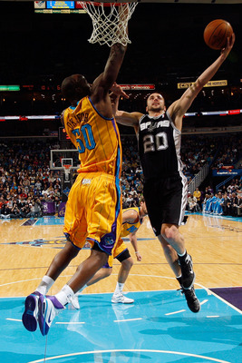NEW ORLEANS, LA - JANUARY 22:  Manu Ginobili #20 of the San Antonio Spurs shoots the ball over Emeka Okafor #50 of the New Orleans Hornets at the New Orleans Arena on January 22, 2011 in New Orleans, Louisiana.  NOTE TO USER: User expressly acknowledges a