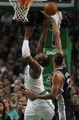BOSTON, MA - JANUARY 05:  Glen Davis #11 of the Boston Celtics takes a shot as Tim Duncan #21 of the San Antonio Spurs defends on January 5, 2011 at the TD Garden in Boston, Massachusetts. The Celtics defeated the Spurs 105-103. NOTE TO USER: User express