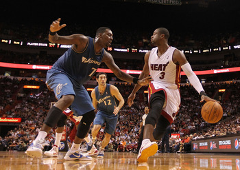 MIAMI, FL - NOVEMBER 29:  Dwyane Wade #3 of the Miami Heat dribbles around Andray Blatche #7 of the Washington Wizards  during a game at American Airlines Arena on November 29, 2010 in Miami, Florida. NOTE TO USER: User expressly acknowledges and agrees t