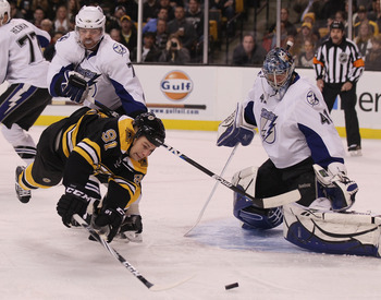 BOSTON, MA - DECEMBER 02:  Marc Savard #91 of the Boston Bruins tries to get a shot past Mike Smith #41 of the Tampa Bay Lightning as Brett Clark #7 of the Lightning defends on December 2, 2010 at the TD Garden in Boston, Massachusetts.  (Photo by Elsa/Ge