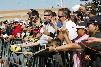 KANSAS CITY, KS - OCTOBER 01:  Fans look to get autographs during practice for the NASCAR Sprint Cup Series Price Chopper 400 on October 1, 2010 in Kansas City, Kansas.  (Photo by Christa Thomas/Getty Images for NASCAR)