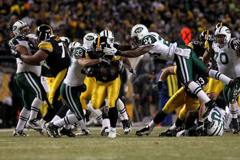 PITTSBURGH, PA - JANUARY 23:  Rashard Mendenhall #34 of the Pittsburgh Steelers tries to avoid the tackle of James Ihedigbo #44 and Darrelle Revis #24 of the New York Jets during the 2011 AFC Championship game at Heinz Field on January 23, 2011 in Pittsbu