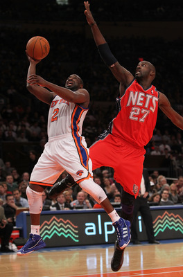 NEW YORK, NY - NOVEMBER 30:  Raymond Felton #2 of the New York Knicks shoots the ball under the block of Johan Petro #27 of the New Jersey Nets on November 30, 2010 at Madison Square Garden in New York City. NOTE TO USER: User expressly acknowledges and a