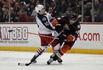 ANAHEIM, CA - JANUARY 07:  Joffrey Lupul #19 of the Anaheim Ducks is hit by Kris Russel #10 of the Columbus Blue Jackets in the third period at the Honda Center on January 7, 2011 in Anaheim, California. The Ducks defeated the Blue Jackets 6-0.  (Photo by