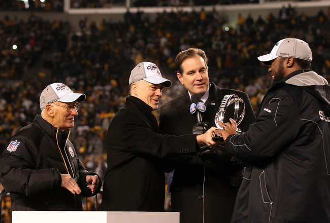PITTSBURGH, PA - JANUARY 23:  Owner Dan Rooney (L), Team president Art Rooney II (2ndL),  and head coach Mike Tomlin (R) of the Pittsburgh Steelers recieve the Lamar Hunt Trophy as CBS sportscaster Jim Nantz looks on after their 24 to 19 win over the New