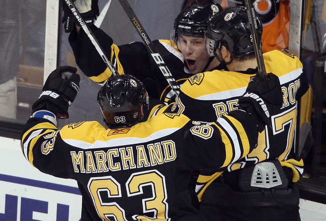 BOSTON, MA - JANUARY 13:   Steven Kampfer #47 of the Boston Bruins is congratulated by Brad Marchand #63 and Patrice Bergeron #37 after Kampfer scored the game winner against the Philadelphia Flyers on January 13, 2011 at the TD Garden in Boston, Massachu