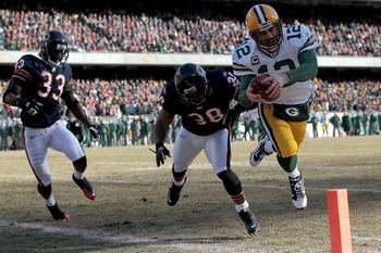 CHICAGO, IL - JANUARY 23:  Quarterback Aaron Rodgers #12 of the Green Bay Packers dives into the corner of the endzone for a one-yard touchdown run against Danieal Manning #38 of the Chicago Bears in the first quarter of the NFC Championship Game at Soldi