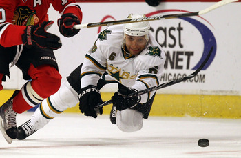 CHICAGO, IL - JANUARY 05: Trevor Daley #6 of the Dallas Stars falls to ice after trying to knock the puck away from Patrick Sharp of the Chicago Blackhawks at the United Center on January 5, 2011 in Chicago, Illinois. (Photo by Jonathan Daniel/Getty Image