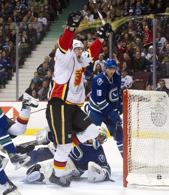 VANCOUVER, CANADA - JANUARY 22: Tim Jackman #15 of the Calgary Flames celebrates after scoring against goalie Roberto Luongo #1 of the Vancouver Canucks during the third period in NHL action on January 22, 2011 at Rogers Arena in Vancouver, British Columb
