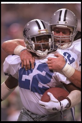 30 Jan 1994: Running back Emmitt Smith of the Dallas Cowboys celebrates with teammate fullback Daryl Johnston during Super Bowl XXVIII against the Buffalo Bills at the Georgia Dome in Atlanta, Georgia. The Cowboys won the game, 30-13.