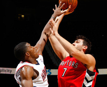 ATLANTA - DECEMBER 02:  Joe Johnson #2 of the Atlanta Hawks defends a shot by Andrea Bargnani #7 of the Toronto Raptors at Philips Arena on December 2, 2009 in Atlanta, Georgia.  NOTE TO USER: User expressly acknowledges and agrees that, by downloading an