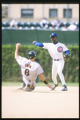 19 May 1997: Shortstop Shawn Dunston of the Chicago Cubs throws the ball as first baseman J.T. Snow of the San Francisco Giants slides at Wrigley Field in Chicago, Illinois. The Cubs won the game 15-4.