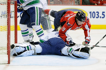 WASHINGTON - JANUARY 14:  Nicklas Backstrom #19 of the Washington Capitals crashes into Roberto Luongo #1 of the Vancouver Canucks at the Verizon Center on January 14, 2011 in Washington, DC.  (Photo by Greg Fiume/Getty Images)
