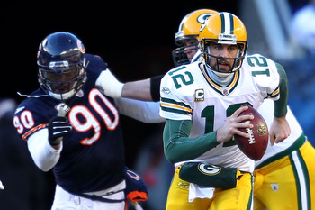 CHICAGO, IL - JANUARY 23:  Quarterback Aaron Rodgers #12 of the Green Bay Packers runs the ball ahead of Julius Peppers #90 of the Chicago Bears in the NFC Championship Game at Soldier Field on January 23, 2011 in Chicago, Illinois.  (Photo by Andy Lyons/