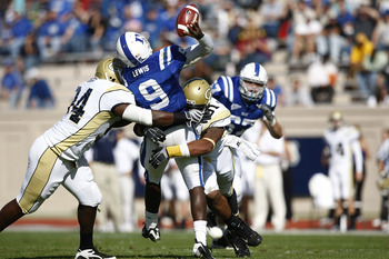 DURHAM, NC - NOVEMBER 14:  Thaddeus Lewis #9 of the Duke Blue Devils throws a pass while being hit by Izaan Cross #94 and Derrick Morgan #91 of the Georgia Tech Yellow Jackets during first half action at Wallace Wade Stadium on November 14, 2009 in Durham