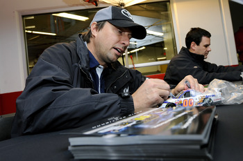 DAYTONA BEACH, FL - JANUARY 21:  David Reutimann, driver of the #00 Aaron's Toyota, signs autographs for some race fans after testing at Daytona International Speedway on January 21, 2011 in Daytona Beach, Florida.  (Photo by Jared C. Tilton/Getty Images