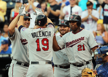 KANSAS CITY, MO - JULY 26:  Danny Valencia #19 of the Minnesota Twins is congratulated by teammates Joe Mauer #7, Jason Kubel #16 and Delmon Young #21 at home plate after hitting a grand slam home run during the 1st inning of the game against the Kansas C
