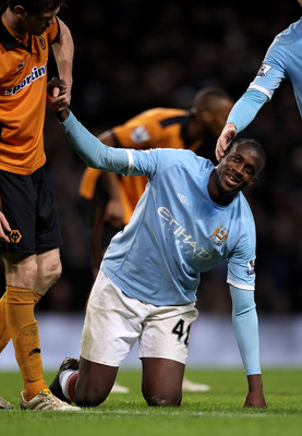 MANCHESTER, ENGLAND - JANUARY 15:   Yaya Toure of Manchester City is helped to his feet during the Barclays Premier League match between Manchester City and Wolverhampton Wanderers at the City of Manchester Stadium on January 15, 2011 in Manchester, Engla