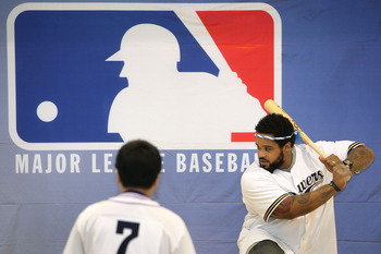 TOKYO - DECEMBER 15:  Prince Fielder of the Milwaukee Brewers displays his batting skills to a member of the baseball club while visiting Minamisuna Junior High School as part of the Major League Baseball (MLB) International Ambassador program to promote