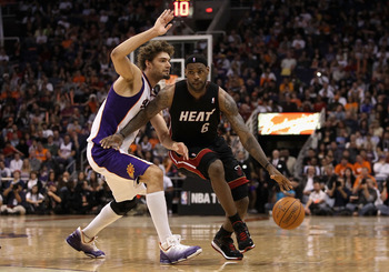 PHOENIX - DECEMBER 23:  LeBron James #6 of the Miami Heat drives the ball past Robin Lopez #15 of the Phoenix Suns during the NBA game at US Airways Center on December 23, 2010 in Phoenix, Arizona. The Heat defeated the Suns 95-83.  NOTE TO USER: User exp