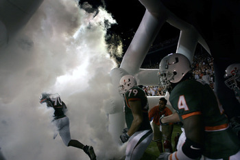 MIAMI - OCTOBER 14:  University of Miami football players run through smoke before the start of their game against the University of Louisville on October 14, 2004 at the Orange Bowl in Miami, Florida.  (Photo by Eliot J. Schechter/Getty Images)